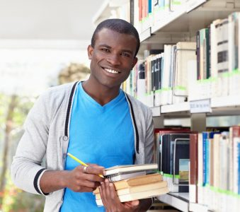young african man smiling in library